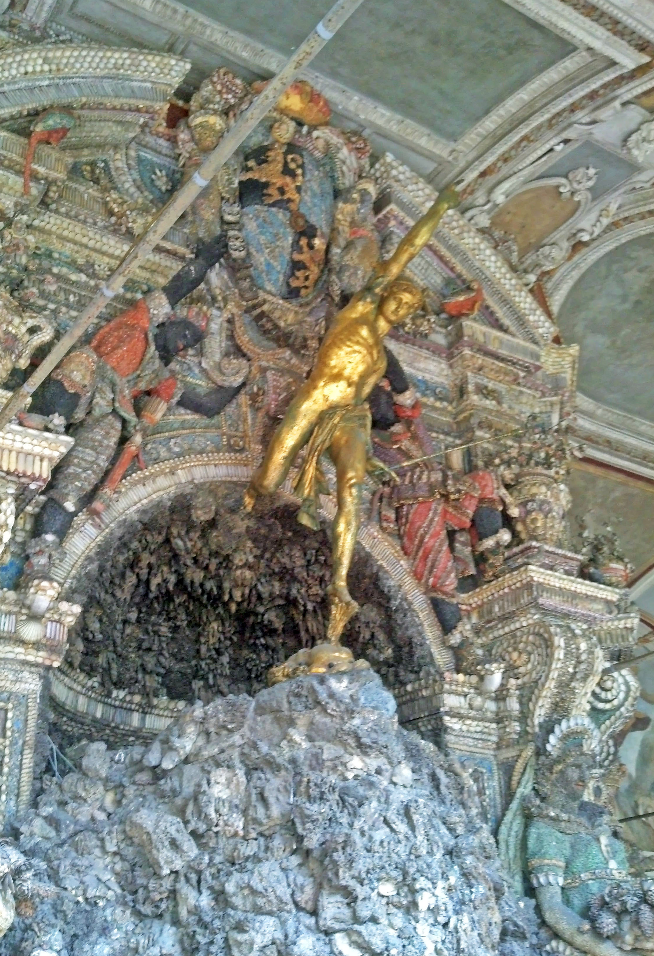 A golden statue of Mercury in the Shell Grotto.